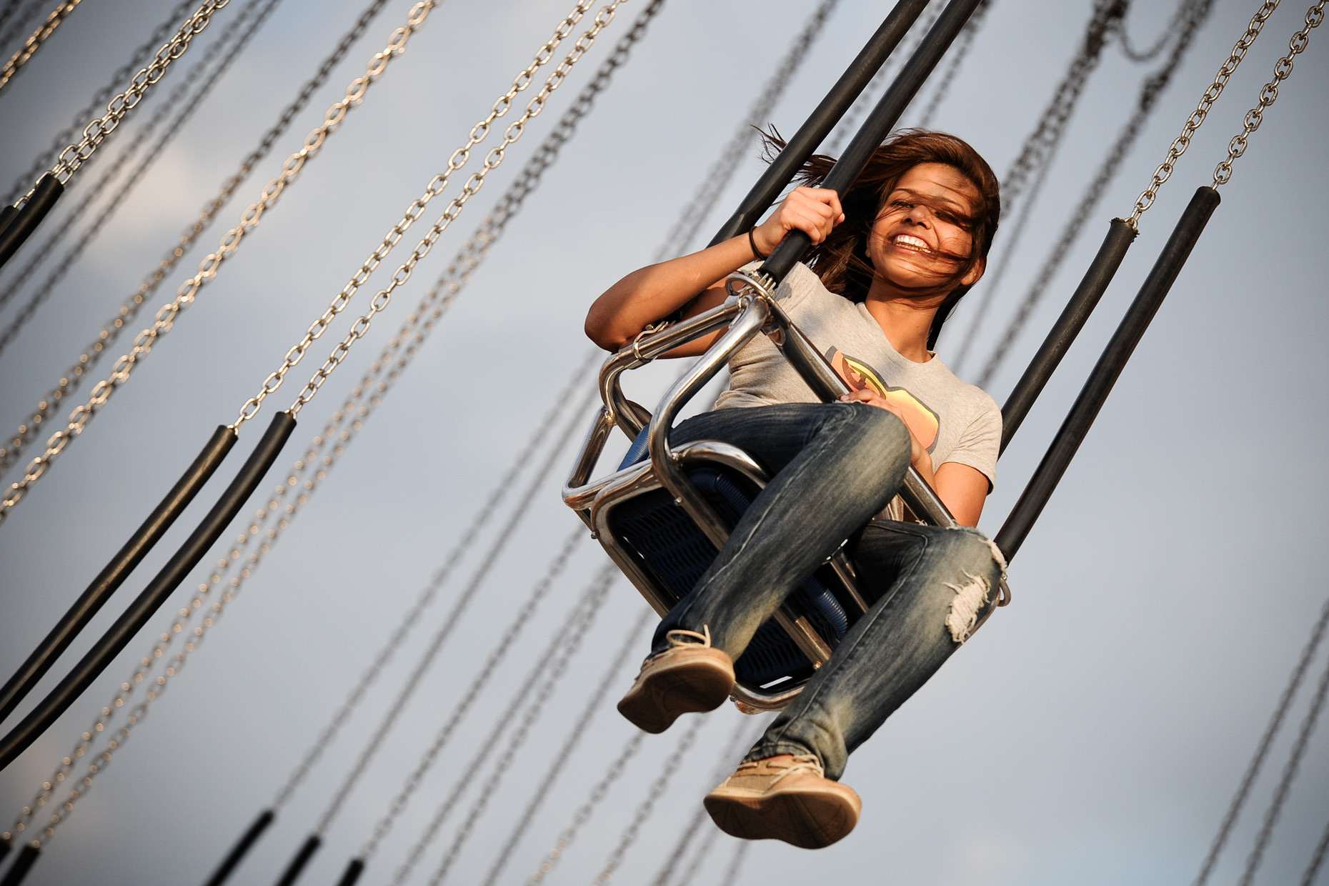 Girl on swings at The State Fair of Texas. Photography by Kevin Brown